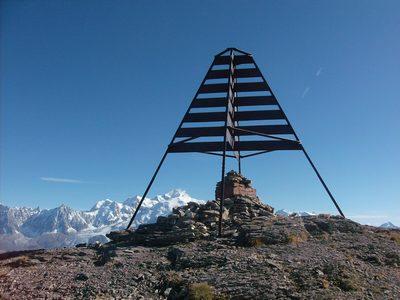La borne sommitale devant le massif du Mont Blanc.